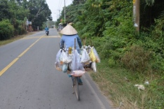 Woman riding home with fish from market in tow